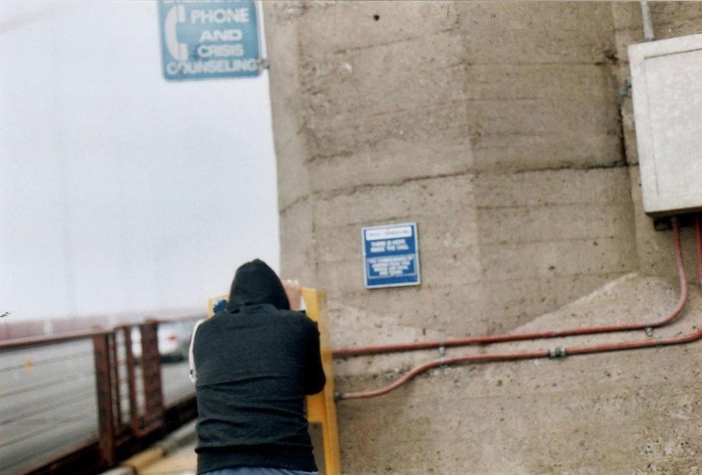 Un uomo usa la linea verde per i suicidi al ponte Golden Gate, tra la baia di San Francisco e l'Oceano Pacifico.