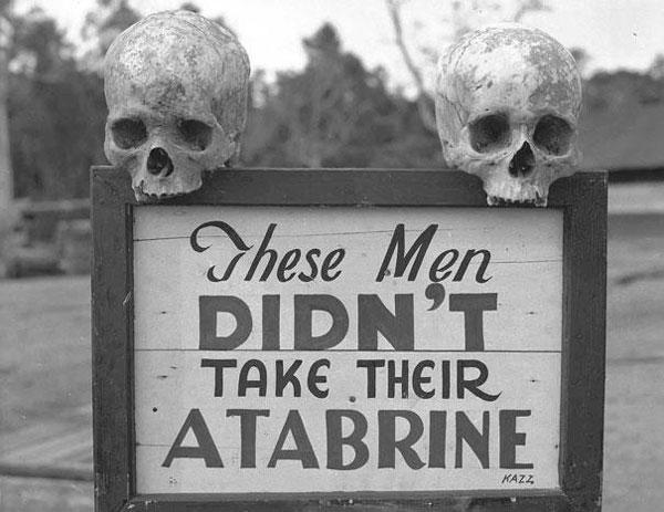 """Una pubblicità macabra dell'Atabrine, un farmaco contro la malaria usato durante la seconda guerra mondiale. Il cartello recita: """"Questi uomini non hanno preso la loro Atabrine"""""""