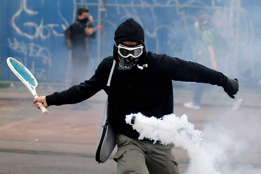 Manifestante che prende di rimbalzo con una racchetta da tennis un fumogeno